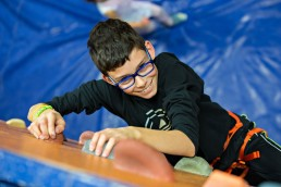 Boy on bouldering wall in climbing gym